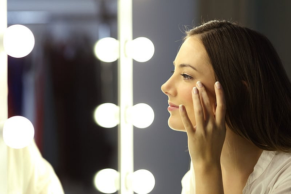 Side view portrait of a single woman checking for wrinkles looking at a make up mirror